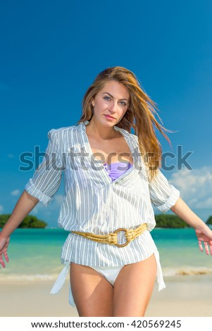 woman on the tropical  beach in white shirt