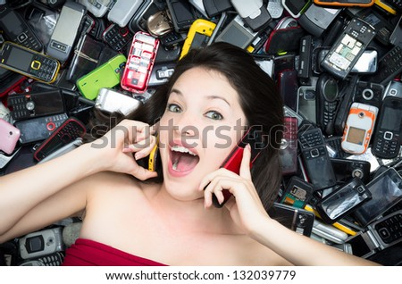 Woman on top of a Pile of mobile cell phones, logos and TRADEMARK romoved - stock photo