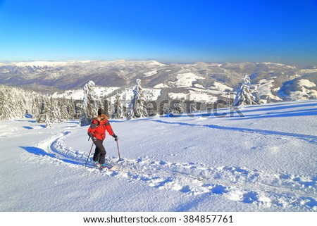 Woman on touring skis ascending on deep snow in sunny winter day - stock photo