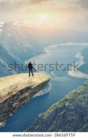 Woman On Trolltunga -  View On Norway Mountain Landscape At Sunset From Trolltunga - The Troll's tongue in Odda, Ringedalsvatnet Lake,  Norway). - stock photo