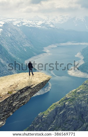 Woman On Trolltunga -  View On Norway Mountain Landscape From Trolltunga - The Troll's tongue in Odda, Ringedalsvatnet Lake,  Norway). - stock photo