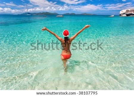 woman on tropical beach with christmas hat