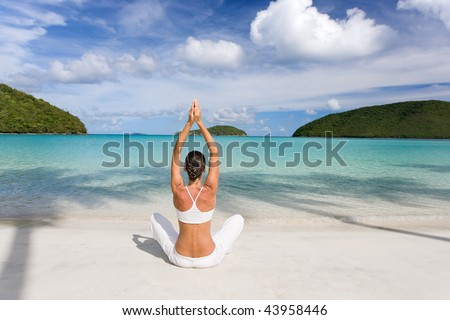 woman on tropical resort beach doing yoga relaxing - stock photo