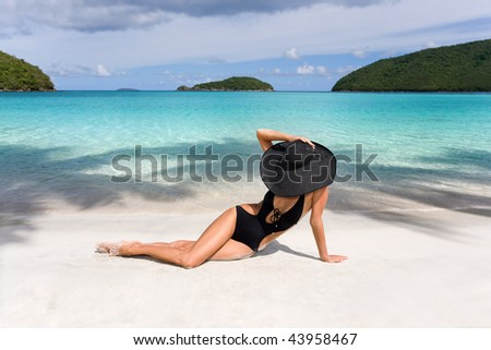 woman on tropical resort beach in elegant black wide brim hat in caribbean exotic luxury island - stock photo