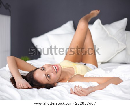 Woman on underwear is lying in the comfortable bed - stock photo