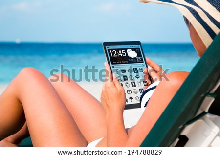 Woman on vacation lies in a sun lounger on the beach with a tablet in hands. - stock photo