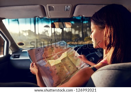 Woman on vacation looking at map for directions while driving in car - stock photo