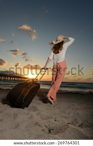 Woman on vacation looking at the ocean during a sunrise with a pier in background - stock photo