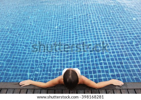 Woman on vacation sitting in swimming pool - stock photo
