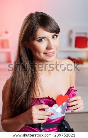 woman on Valentine's Day with a paper heart with a ship. - stock photo