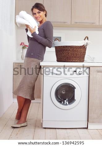 woman on washing machine in kitchen - stock photo
