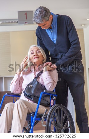 Woman on wheelchair with male assistant in hospital room.