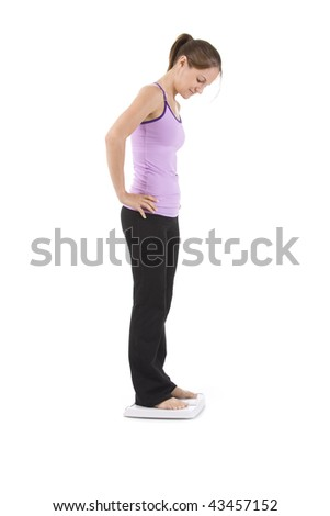 Woman on white standing on scale looking happy. - stock photo