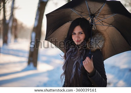 Woman on winter park with umbrella