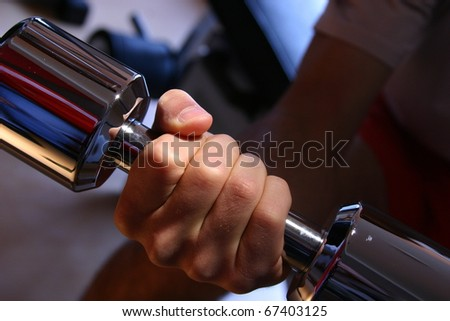 woman (only arms and body) training with dumbbells (focus on weight, shallow depth of field - stock photo