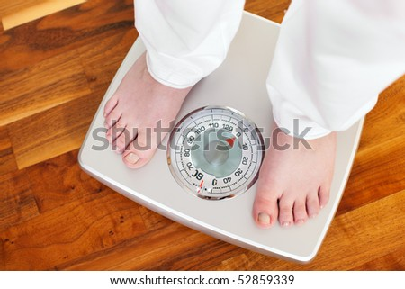 Woman (only feet to be seen) standing on bathroom scale measuring her weight controlling her dieting results