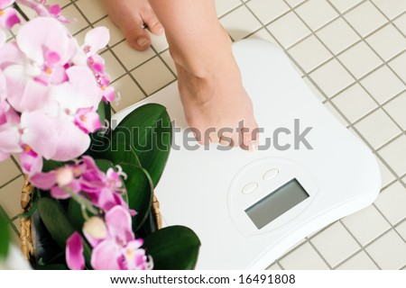 Woman (only feet to be seen) stepping on a scale in a spa setting - stock photo
