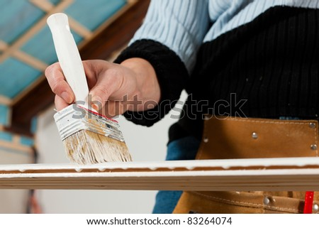 woman - only hands to be seen -  is painting in her house; presumably she is renovating - stock photo