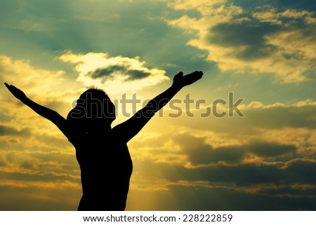 woman open arms under the sunrise at sea