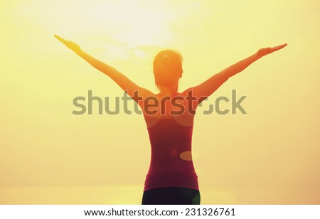 woman open arms under the sunrise at seaside - stock photo