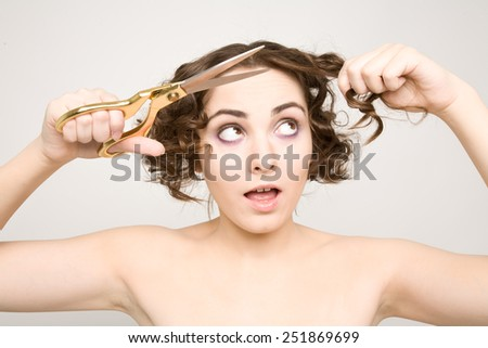 Woman open her mouth and cutting her curly hair - stock photo
