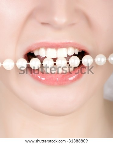 Woman open mouth and teeth biting on faux pearls - stock photo