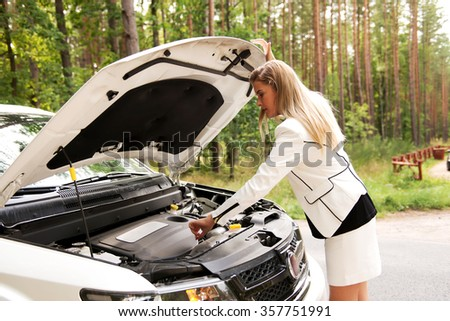 Woman opened the hood broken car. - stock photo