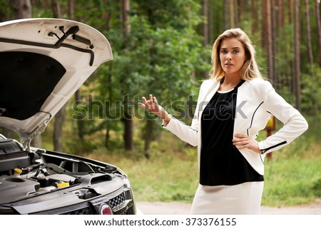 Woman opened the hood broken car - stock photo