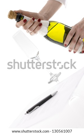 Woman opening a bottle of wine on a table with signed contract. Concept of celebrating successful agreement.