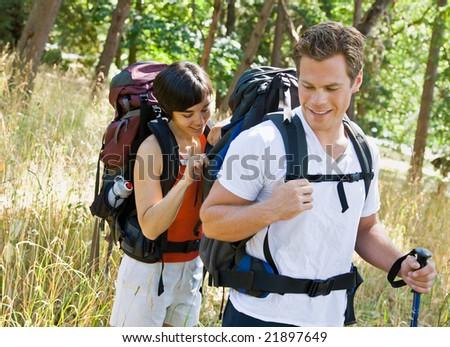 Woman opening boyfriends backpack - stock photo
