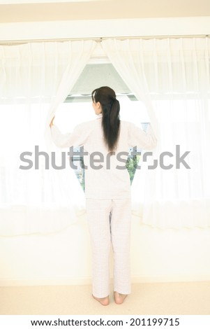 Woman opening the curtain