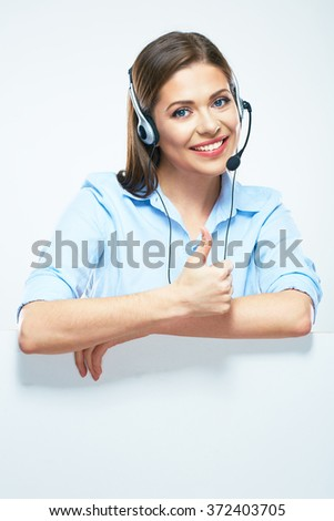 Woman operator with headset and blank sign board showing thumbs up. Isolated portrait of smiling help line operator. - stock photo