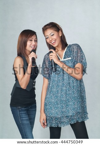 Woman or asian girls with a microphone singing