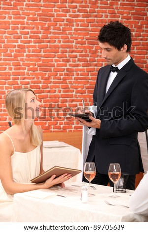 Woman ordering at a restaurant - stock photo