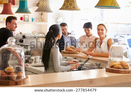 Woman ordering at the counter in a cafe - stock photo