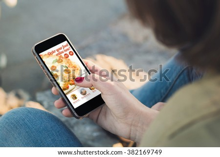 woman ordering fast food with her smartphone and touching the screen. All screen graphics are made up. - stock photo