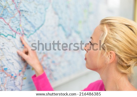Woman orientating herself on the public transport map pointing on her final destination. - stock photo