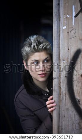 woman outdoor, looking at the camera, hidding behind a wall - stock photo