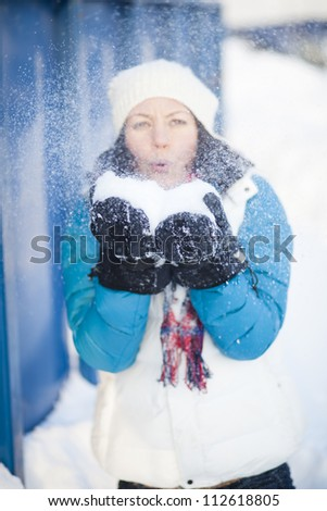 Woman outdoors blowing snow on a cold winter day