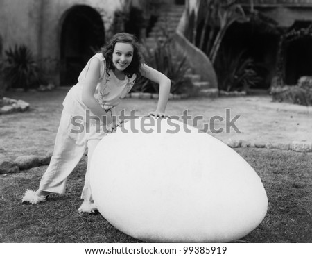 Woman outside with giant egg - stock photo