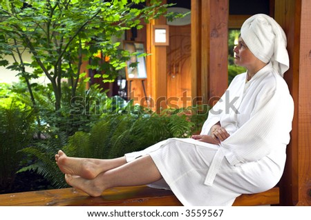 woman outside with robe resting and enjoying a spa resource - stock photo