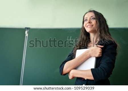 woman over green  chalkboard reading book