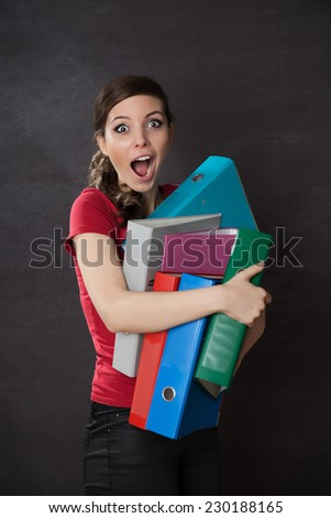 Woman overloaded with work. Chalkboard background - stock photo