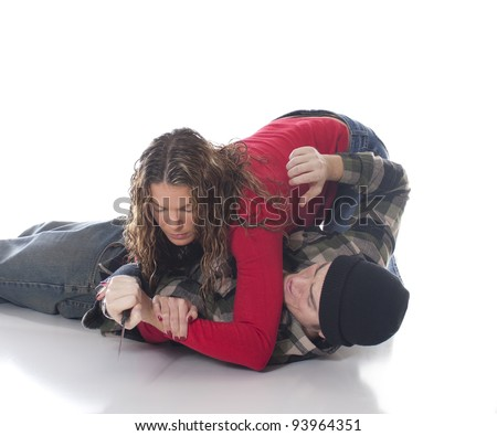 Woman overpowering a mugger with knife using a a joint lock - stock photo