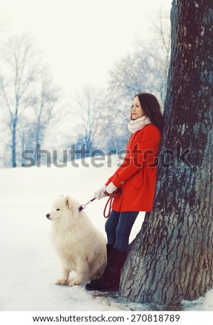 Woman owner and white Samoyed dog near tree in the winter park - stock photo