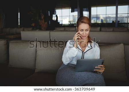 Woman owner takes order from client via mobile phone for conduct of corporate party while sitting in her restaurant, young female looking at digital tablet screen while talking via cell telephone  - stock photo