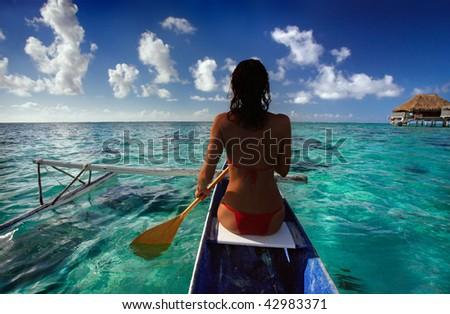 Woman paddling canoe in Tahiti - stock photo