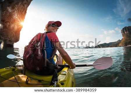 Woman paddling the sea kayak in the tropical calm lagoon with mountains - stock photo