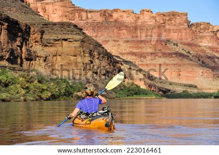 Woman paddling touring kayak in Cayonlands National Park - stock photo