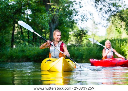 Woman paddling with canoe on forest river - stock photo